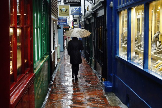 A woman carrying an umbrella walks through The Lanes shopping area in Brighton, southern England, in this January 8, 2015 file photo. Boasting distinctive attractions, the city is an hour's train ride south of London and enjoys one of the sunniest climates in Britain. (Photo by Luke Macgregor/Reuters)