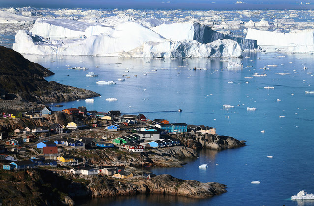 The village of Ilulissat is seen near the icebergs that broke off from the Jakobshavn Glacier, on July 24, 2013 in Ilulissat, Greenland. Researchers affiliated with the National Science Foundation and other organizations are studying the phenomena of melting glaciers and its long-term ramifications. (Photo by Joe Raedle/Getty Images via The Atlantic)