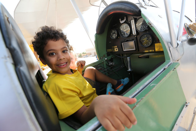 A boy sits in a biplane after 18 biplanes landed at Khartoum Airport in Sudan during a tour across Africa, November 20, 2016. (Photo by Mohamed Nureldin Abdallah/Reuters)