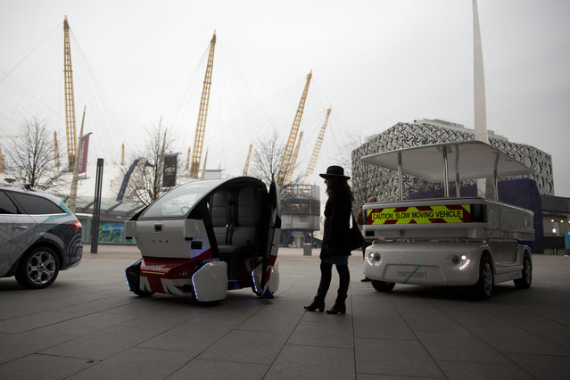 A woman poses for photographers beside a prototype driverless car called a LUTZ (Low-carbon Urban Transport Zone) Pathfinder Pod, center, and a Meridian shuttle, right, during a launch event for the media near the O2 Arena in London, Wednesday, February 11, 2015.  Britain has begun testing driverless cars in four cities, launching the first official trials ahead of a series of planned rule reviews to accommodate the new technology. (Photo by Matt Dunham/AP Photo)