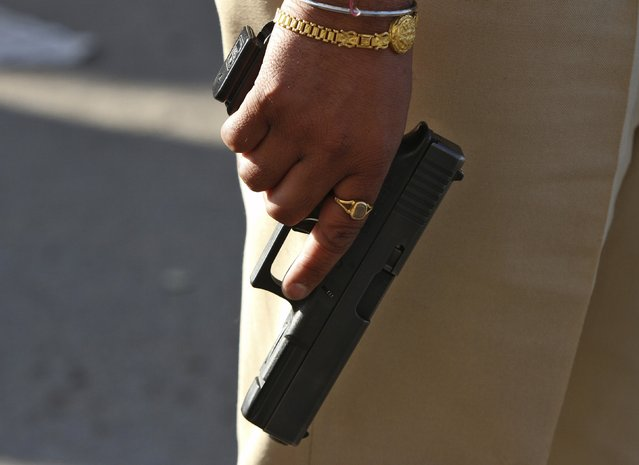 An Indian security personnel carries a pistol while standing on guard outside the Indian Air Force (IAF) base at Pathankot in Punjab, India, January 2, 2016. At least two gunmen and a guard were killed in an attack on an Indian Air Force base on Saturday near the border with Pakistan, officials said, in an apparent challenge to attempts to revive a dialog between the nuclear-armed neighbors. (Photo by Mukesh Gupta/Reuters)