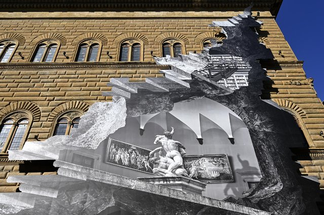 "A general view shows visual installation ""La Ferita"" (The Wound) by French artist JR after its unveiling on the facade of the Renaissance Palazzo Strozzi in Florence on March 19, 2021. JR has reinterpreted the façade of the Renaissance palazzo with one of his signature optical illusions, appearing to open up the building to reveal a vision of an interior at once real and imaginary achieved with a black and white photographic collage to trigger a debate on the accessibility of culture in the age of Covid-19. (Photo by Alberto Pizzoli/AFP Photo)"