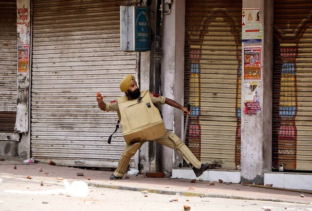 A policeman throws stones at Hindus protesting against the state government after rival communities clashed in Kishtwar, in Jammu, India, on August 10, 2013. Indian forces fired warning shots Saturday to enforce a curfew and to push angry people back into their homes in Kishtwar, in the Indian portion of Kashmir where clashes between Muslims and Hindus during Eid celebrations killed at least two people and injured another 24. (Photo by Channi Anand/Associated Press)