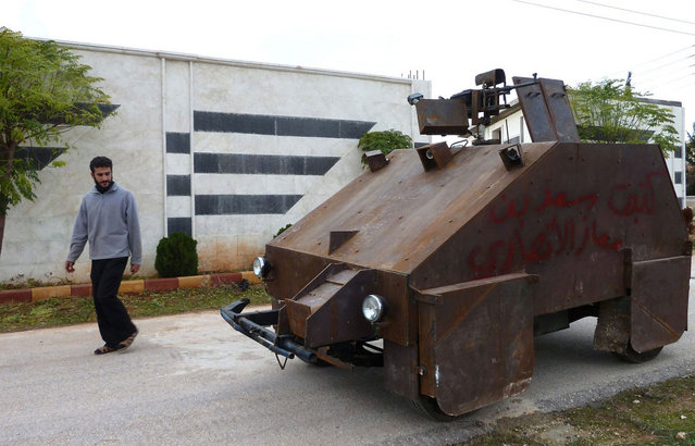 "A Syrian rebel walks past Sham 2, a homemade armored vehicle, in Bishqatin, Syria, on December 8, 2012. From a distance it looks rather like a big rusty metal box but closer inspection reveals a homemade armored vehicle waiting to be deployed. Sham II, named after ancient Syria, is built from the chassis of a car and touted by rebels as ""100 percent made in Syria"". (Photo by Herve Bar/AFP Photo)"