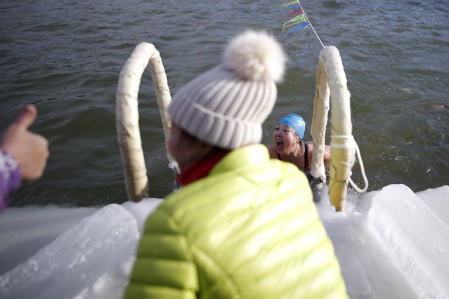 A female swimmer reacts after finishing the competition in a pool carved from thick ice covering the Songhua River during the Harbin Ice Swimming Competition in the northern city of Harbin, Heilongjiang province, January 5, 2016. The swimming competition was held on the official launch day of the Harbin International Ice and Snow Sculpture Festival. (Photo by Aly Song/Reuters)