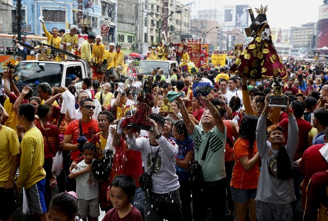 Devotees hold up religious statues as they are sprinkled with holy water two days before the annual procession of the Black Nazarene in Manila January 7, 2016. (Photo by Erik De Castro/Reuters)