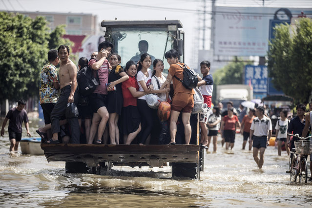 People stand on a front loader in a flooded road at Chendian Town after a heavy rainstorm on September 2, 2018 in Shantou, Guangdong Province of China. Heavy rainstorm hit Shantou, causing direct economic losses worth 2.35 billion yuan (344 million dollars). (Photo by VCG/VCG via Getty Images)