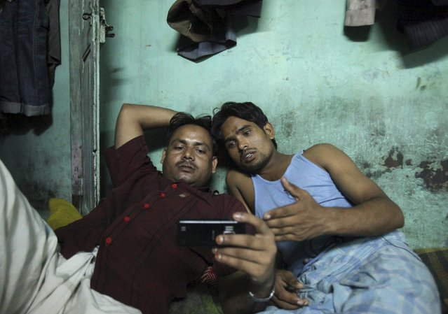 Migrant workers watch movie on a mobile phone in their one room dwelling in a residential area in Mumbai in this October 3, 2011 file photo. (Photo by Danish Siddiqui/Reuters)