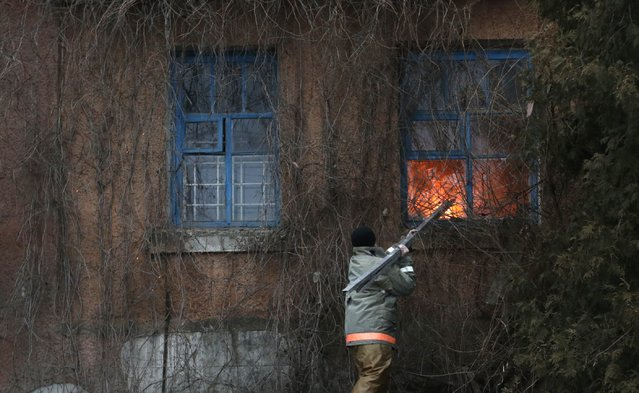 A firefighter attempts to break a window to extinguish a building on fire after shelling between Russian-backed separatists and Ukrainian government in residential area of the town of  Artemivsk, Ukraine, Saturday, February 14, 2015. (Photo by Petr David Josek/AP Photo)