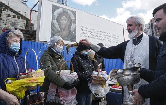 An Orthodox priest blesses traditional Easter cakes and painted eggs prepared for Easter celebration at a church in St. Petersburg, Russia, Saturday, May 1, 2021. Eastern Orthodox churches observe the ancient Julian calendar, and this year celebrate the Orthodox Easter on May 2. (Photo by Dmitri Lovetsky/AP Photo)