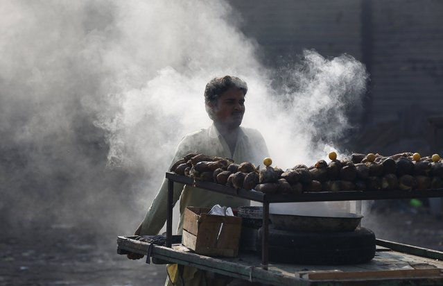 A vendor sells yams and sweet potatoes from his pushcart along a street in a low income neighborhood in Karachi, Pakistan, December 30, 2015. (Photo by Akhtar Soomro/Reuters)