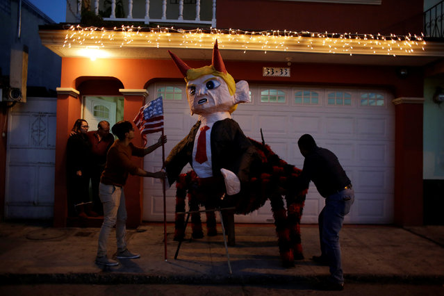Men fix a pinata representing U.S. President-elect Donald Trump as a devil outside a house before it is set on fire at the traditional Burning of the Devil festival, ahead of Christmas in Guatemala City, Guatemala, December 7, 2016. (Photo by Luis Echeverria/Reuters)