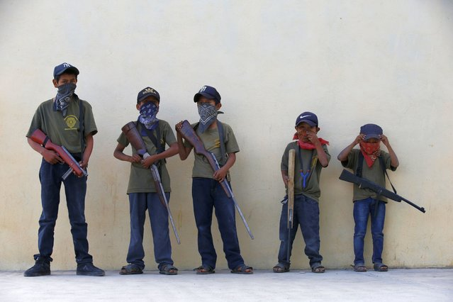 """Children hold their training weapons, some real and some fake, during a display for the media designed to attract the federal government's attention to the dangers of organized crime that their town negotiates daily in Ayahualtempa, Guerrero state, Mexico, Wednesday, April 28, 2021. International organizations have condemned the """"recruitment"""" of children and warned of the effects. (Photo by Marco Ugarte/AP Photo)"""