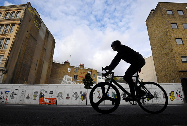 A cyclist rides past a boarded-up petrol station, used as an open-air cinema as well as a car wash since its closure, now awaiting commercial redevelopment in a prime real estate location in the Clerkenwell district of central London, Britain, October 26, 2016. (Photo by Toby Melville/Reuters)