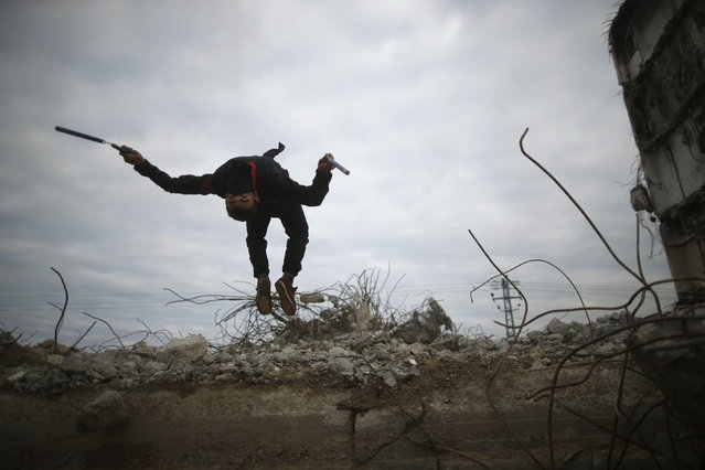 A Palestinian youth jumps as he demonstrates his ninja-style skills for a photographer at the ruins of a building, that was destroyed in the 2014 war, in the northern Gaza Strip January 29, 2016. (Photo by Mohammed Salem/Reuters)