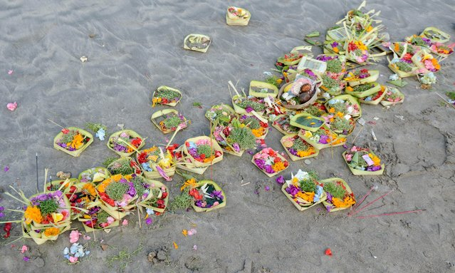 "Offerings are placed by the shoreline after prayers during the Melasti ceremony at Kuta beach on the island of Bali on March 18, 2015. Melasti is a purification festival which is held several days before ""Nyepi"", a day of silence, when Hindus on the island of Bali are not allowed to work, travel or take part in any indulgence. The Indonesian holiday island of Bali shuts down for the day of silence to mark the Hindu new year. (Photo by Sonny Tumbelaka/AFP Photo)"