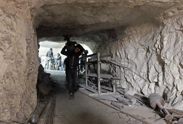 A man carries a locally made shell as he walks inside a cave used as a weapon factory operated by rebel fighters from Suqour al-Sham Brigade in Idlib countryside March 18, 2015. (Photo by Mohamad Bayoush/Reuters)