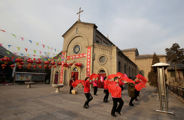 Villagers dance during a rehearsal before performing on the Christmas Eve, outside of a Catholic church on the outskirts of Taiyuan, North China's Shanxi province, December 23, 2016. (Photo by Jason Lee/Reuters)