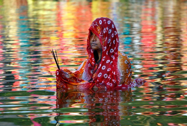 A Hindu woman worships the Sun god in the waters of a lake during the religious festival of Chhath Puja in Agartala, India, November 13, 2018. (Photo by Jayanta Dey/Reuters)