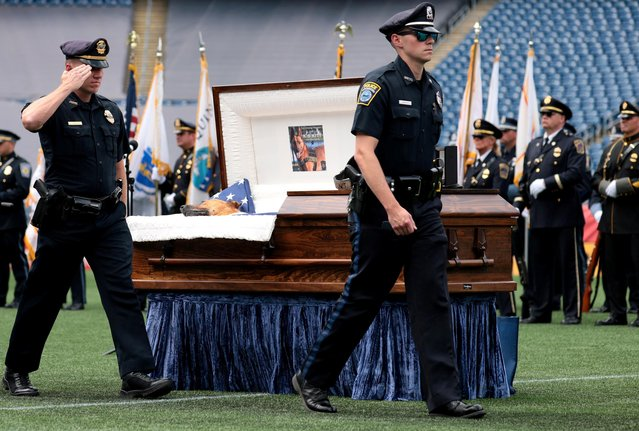 Police officers salute the casket of K-9 Kitt in Gillette Stadium during a memorial service held in honor of the police dog, who was killed during a domestic violence call, in Boston, Massachusetts, U.S. June 22, 2021. (Photo by Jessica Rinaldi/Pool via Reuters)