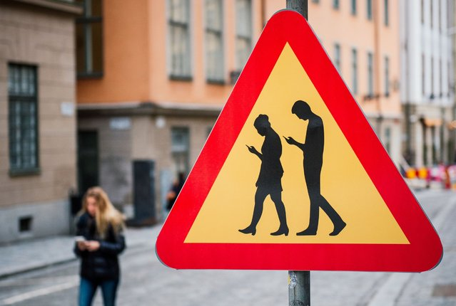 A road sign arning against pedestrians focusing on their smartphones is pictured on February 2, 2016 near the old town in Stockholm. (Photo by Jonathan Nackstrand/AFP Photo)