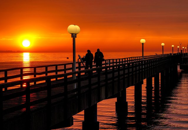 People walk on the pier at the Baltic Sea in Scharbeutz, Germany, as the sun rises Monday, June 7, 2021. (Photo by Michael Probst/AP Photo)