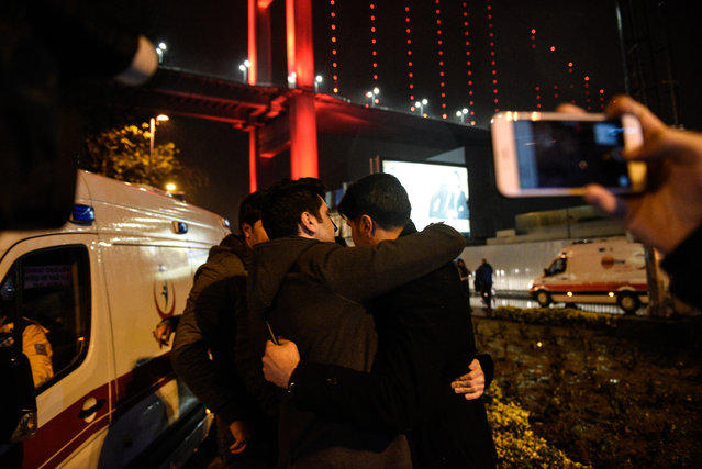 Youths embrace near the scene of an attack in Istanbul, on New Year's Day, early Sunday, January 1, 2017. An assailant believed to have been dressed in a Santa Claus costume and armed with a long-barrelled weapon, opened fire at a nightclub in Istanbul's Ortakoy district during New Year's celebrations, killing dozens of people and wounding dozens of others in what the province's governor described as a terror attack. (Photo by Depo Photos via AP Photo)