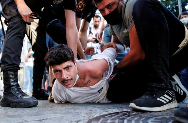 Police detain an activist during a protest, on the anniversary of a bomb attack that killed 34 people in 2015 in the south-eastern Turkish town of Suruc, in Istanbul, Turkey, July 20, 2021. (Photo by Kemal Aslan/Reuters)