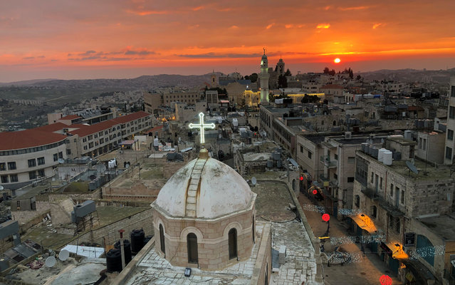 A view shows the dome of the Assyrian church facing a mosque minaret at Manger Square where the Church of the Nativity is located, in Bethlehem in the Israeli-occupied West Bank on December 24, 2018. (Photo by Mustafa Ganeyeh/Reuters)