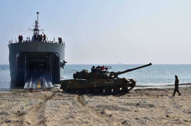A South Korean K-1 tank disembarks from a landing ship tank ship (LST) on a beach during a joint landing operation by US and South Korean Marines in the southeastern port of Pohang on March 30, 2015. The drill is part of the annual joint exercise Foal Eagle to enhance the combat readiness of the US and South Korea supporting forces in defense of the Korean Peninsula. (Photo by Jung Yeon-Je/AFP Photo)