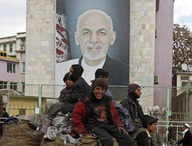 Afghan youths sit on the roof of a car as they pass a picture of Afghan President Ashraf Ghani on a street in Kabul February 19, 2015. Senior Pakistani army and diplomatic officials said on Thursday the Afghan Taliban have signaled through the Pakistani military that they are willing to open peace talks, which could begin later in the day. (Photo by Omar Sobhani/Reuters)