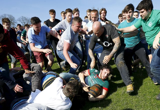 A player falls to the ground with the bottle during the bottle-kicking game in Hallaton, central England April 6, 2015. (Photo by Darren Staples/Reuters)