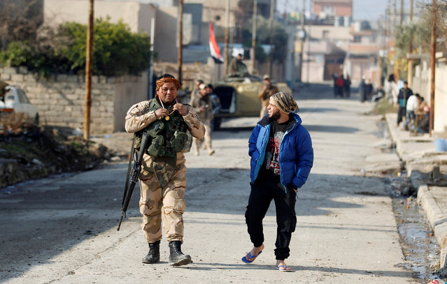 A civilian speaks with a member of the Iraqi rapid response forces during battle with Islamic State militants in the Mithaq district of eastern Mosul, Iraq, January 5, 2017. (Photo by Khalid al Mousily/Reuters)