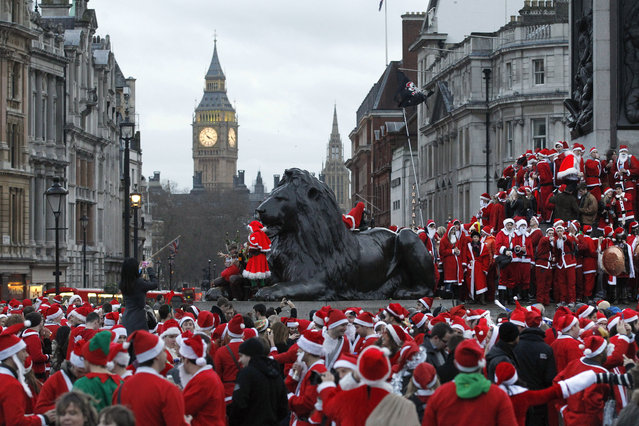 In this December 15, 2012 file photo, revellers dressed up in Santa gather at Trafalgar Square  in London during a SantaCon festival in London. SantaCon events unfold in more than 300 cities worldwide and the New York celebration is one of the biggest, but complaints about boorish, bar-hopping St. Nicks at previous SantaCons got attention from local officials and the NYPD. (Photo by Sang Tan/AP Photo)