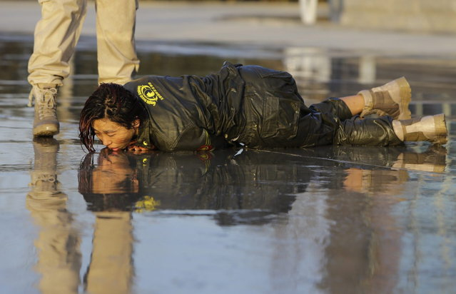 A female trainee lies on the ground after being drenched with water during Tianjiao Special Guard/Security Consultant training on the outskirts of Beijing December 1, 2013. (Photo by Jason Lee/Reuters)