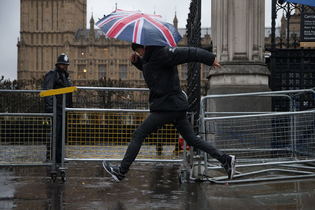 A pedestrian jumps over a puddle on the pavement outside the Houses of Parliament in central London on January 12, 2017. Severe weather warnings were in place as heavy rain, snow and blizzard conditions sweep parts of Britain. (Photo by Daniel Leal-Olivas/AFP Photo)