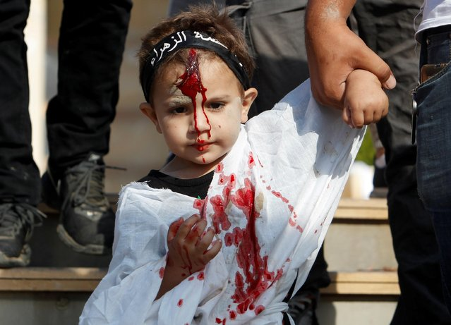 A child is pictured with the face covered in blood during a religious procession to mark Ashura in Nabatieh, southern Lebanon on August 19, 2021. (Photo by Aziz Taher/Reuters)