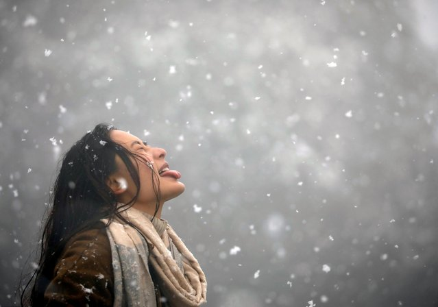 A woman tries to catch snowflakes with her tongue during a snowfall on Chandragiri Hills in Kathmandu, Nepal on January 23, 2019. (Photo by Navesh Chitrakar/Reuters)