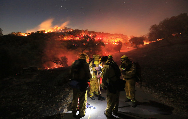 Firefighters from Schell Vista of Sonoma County and Santa Clara County Cal Fire prepare to put out hotspots on a fire in the hills of Soda Canyon above Napa, Calif., Friday, November 22, 2013. (Photo by Kent Porter/AP Photo/Santa Rosa Press Democrat)
