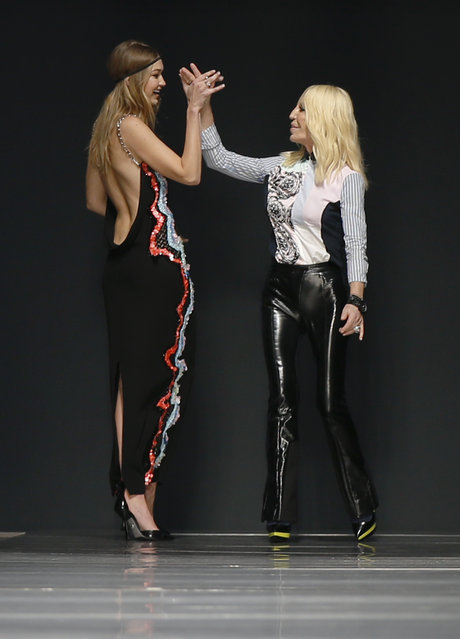 Fashion designer Donatella Versace, right, salutes model Gigi Hadid at the end of the Versace women's Fall-Winter 2016-2017 fashion show, part of the Milan Fashion Week, unveiled in Milan, Italy, Friday, February 26, 2016. (Photo by Luca Bruno/AP Photo)