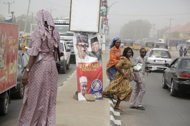 People cross the roads near the Independent National Electoral Commission office in Yola, Nigeria, Friday, February 15, 2019. (Photo by Sunday Alamba/AP Photo)