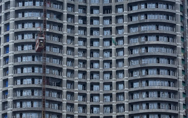 Workers take a lift at an under construction high-rise residential tower in Mumbai's central financial district August 25, 2014. The cost for buying a 2,500 square feet (232 square meters) three-bedroom apartment in this tower is around 70,000 Indian rupees per square feet ($ 1,119) or 175,000,000 Indian rupees ($ 2,798,682). (Photo by Danish Siddiqui/Reuters)
