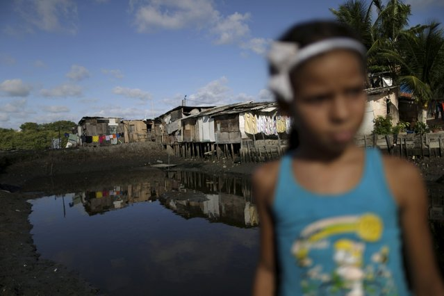 "A child is seen in front of stilt houses at a lake dwelling also known as palafitte or ""Palafito"" in Recife, Brazil, March 1, 2016. (Photo by Ueslei Marcelino/Reuters)"