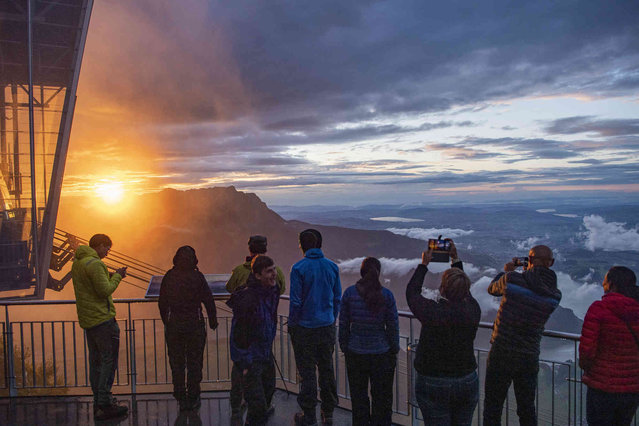 Tourists enjoy the sunset on the Stanserhorn Mountain, with Mount Pilatus and Lake Lucerne in the background, Sunday, August 1, 2021, near Stans, Switzerland. (Photo by Urs Flueeler/Keystone via AP Photo)
