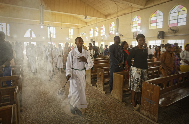 An altar boy swings the thurible of incense during a morning service at the Saint Charles Catholic Church, the site of a 2014 bomb attack blamed on Islamic extremist group Boko Haram, in the predominantly-Christian neighborhood of Sabon Gari in Kano, northern Nigeria Sunday, February 17, 2019. With the leading contenders both northern Muslims, Nigeria's presidential contest has been largely free of the religious pressures that marked the 2015 vote, but the Christian vote is bound to be decisive in a race that could sweep the incumbent out of power. (Photo by Ben Curtis/AP Photo)