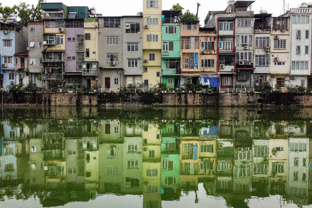 """This photograph taken on June 8, 2021 shows narrow residential houses, known as """"nha ong"""" in Vietnamese or """"tube houses"""", in an urban area of Hanoi. Tall, thin and brightly coloured, Hanoi's """"tube houses"""" dominate the city's streets as nine million people compete for space in the bustling capital. (Photo by Manan Vatsyayana/AFP Photo)"""
