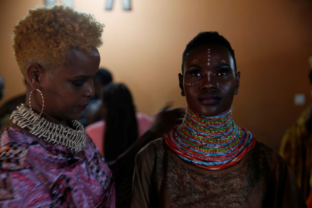 "A model receives final touches behind the scenes of a fashion show featuring African fashion and culture during a gala marking the launch of a book called ""African Twilight: The Vanishing Rituals and Ceremonies of the African Continent"" at the African Heritage House in Nairobi, Kenya on March 3, 2019. (Photo by Baz Ratner/Reuters)"