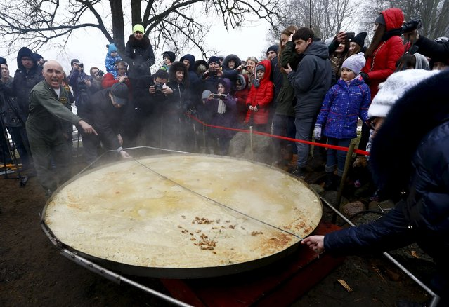 People take the measurements of fried dranik, a potato pancake that is the national dish of Belarus, in the Sula History Park near the village of Sula, Belarus March 7, 2016. According to the park's representatives, the two-metre-wide pancake was an attempt to enter the Guinness World Records as the world's largest dranik. (Photo by Vasily Fedosenko/Reuters)