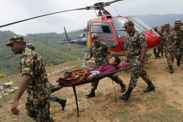 Sita Karka, suffering two broken legs from Saturday's massive earthquake, arrives by helicopter from the heavily-damaged Ranachour village at a landing zone in the town of Gorkha, Nepal, Tuesday, April 28, 2015. (Photo by Wally Santana/AP Photo)