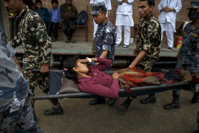 Nepal military personnel carry an earthquake victim on a stretcher as she arrives at the Gorkha hospital in Gorkha, Nepal April 28, 2015. (Photo by Athit Perawongmetha/Reuters)